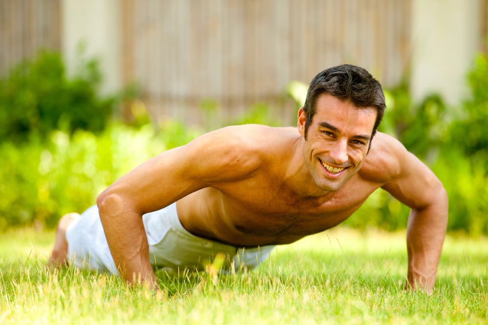 Man doing pushups on grass