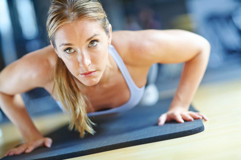 Woman doing pushups on yoga mat