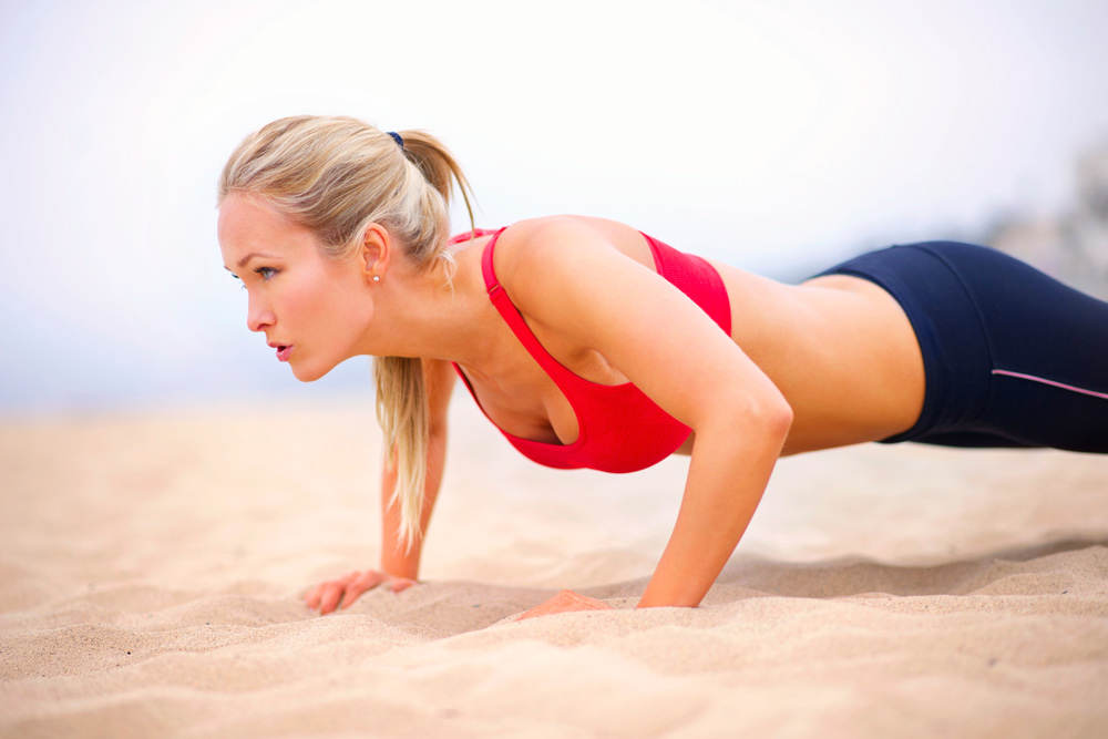 Woman doing pushups on beach